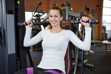 Frau in Fitnesscenter trainiert an Schulterpresse