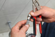 Plumber holding damaged steel flexible metal hose