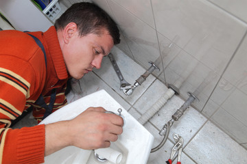 Plumber fixing water tap on bidet in a washroom