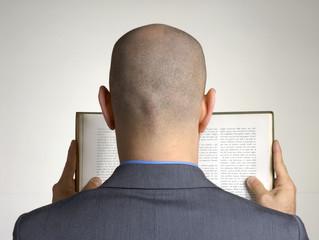 Hombre de espaldas leyendo un libro.