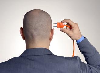 Vista trasera de ejecutivo conectando un enchufe en su cabeza.