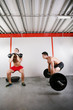 Group of two people exercising using barbells in gym and kettleb