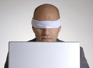 Hombre ejecutivo vendado frente a un ordenador,computador.