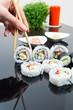 Hand holding stick with maki sushi set