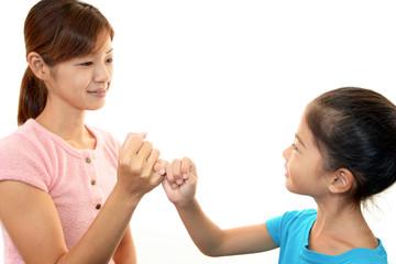 笑顔で指きりをする親子