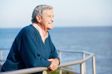 Senior Man Looking Over Railing At Sea