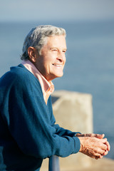 Senior Man Looking Over Railing At Sea