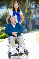 Adult Daughter Pushing Senior Father In Wheelchair