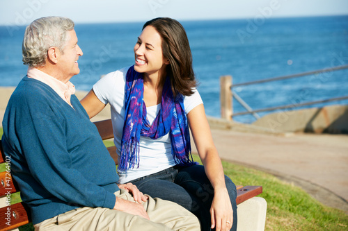 Senior Man Sitting On Bench With Adult Daughter By Sea