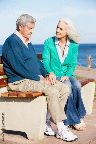 Senior Woman Comforting Depressed Husband Sitting On Bench