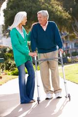 Senior Woman Helping Husband With Walking Frame