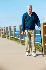Senior Man Walking Along Path By The Sea