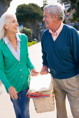 Senior Couple Walking In Park Together With Picnic Basket