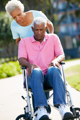 Senior Woman Pushing Unhappy Husband In Wheelchair