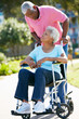 Senior Woman Pushing Unhappy Husband In Wheelchair