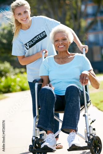 Teenage Volunteer Pushing Senior Woman In Wheelchair