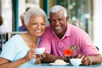 Senior Couple Enjoying Snack At Outdoor Café