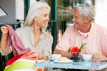Senior Couple Enjoying Snack At Outdoor Café After Shopping
