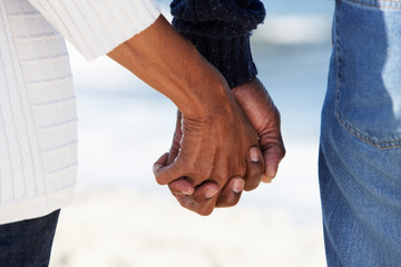 Close Up Of Senior Couple Holding Hands On Beach