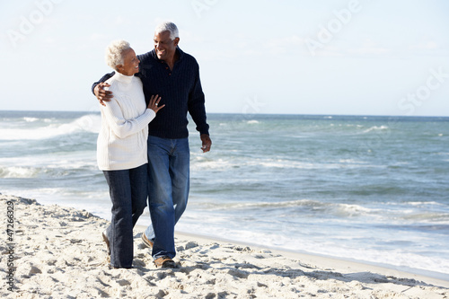 Senior Couple Walking Along Beach Together