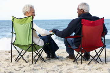 Senior Couple Sitting On Beach In Deckchairs