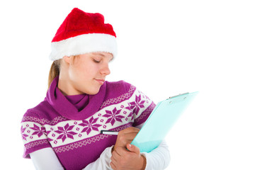 Cute girl with Santa hat writing on paper