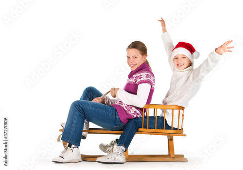 Two cute girls riding on a sledge over a white background