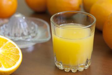 Orange fresh juice with squeezer on table