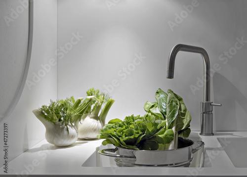 ortaggi sul piano e nel lavandino della cucina moderna