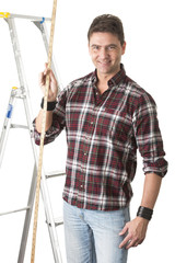 Male builder measuring with wooden rule