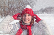 Beautiful woman has a snowball on a red cap