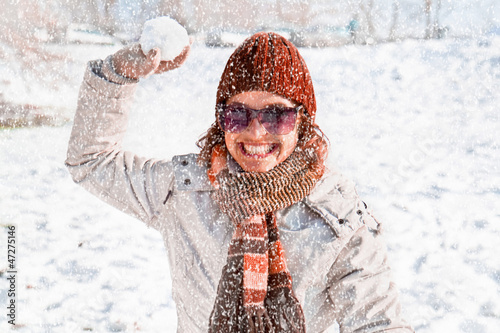 Happy young woman playing snowball fight