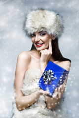 christmas picture of beautiful woman holding a blue present