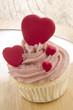 Cupcake mit rosa Buttercreme und roten Herzen