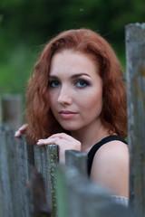 Портрет рыжей девушки у забора в вечерних сумерках