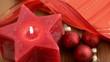 Sternförmige Kerze wird angezündet. Daneben Weinachtsbaumkugeln.