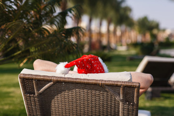 Santa Claus having rest in beach chair over resort background