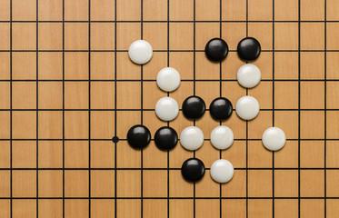 Spielsteine auf einem Go Brett
