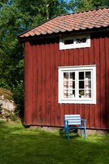 Blauer Stuhl vor rotem Holzhaus
