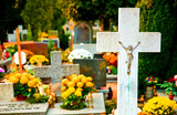 Cross with crucified Jesus Christ and flowers at cemetery