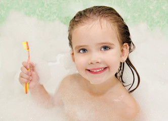Smiling little girl is taking a bath holding toothbrush