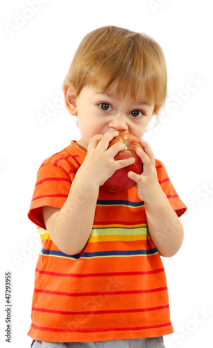 cute little boy eating apple, isolated on white