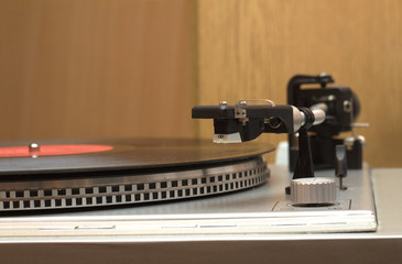 Stereo turntable and vinyl record with red label closeup