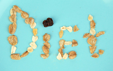 The word Diet laid out on blue bowl of muesli close-up