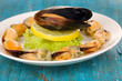 Snack of mussels and lemon on plate on blue wooden table