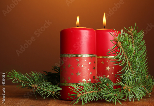 Two candles and christmas tree, on brown background