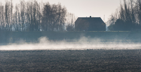 Early morning mist above a plowed field in the Netherlands