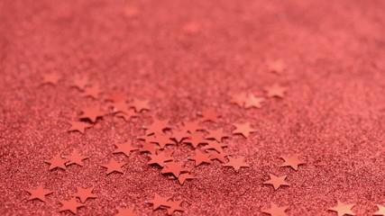 Rote Sterne fallen auf glitzernde rote Folie. Weihnachten.