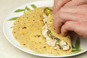 Hands Rolling a Vegetarian Wrap