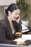 pretty asian businesswoman at computer on phone - smiling
